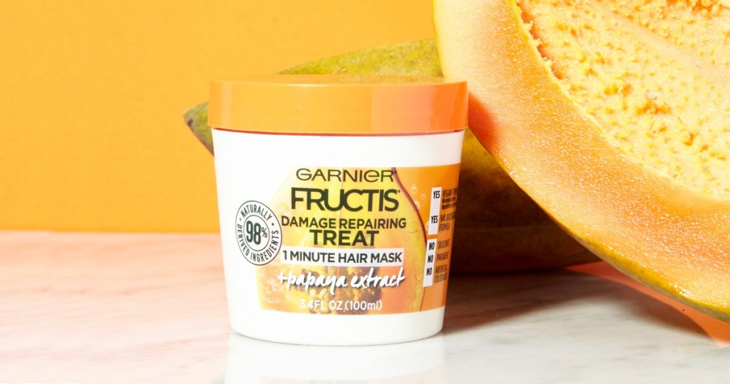 white and orange colored jar of garnier fructis hair mask next to a large papaya fruit