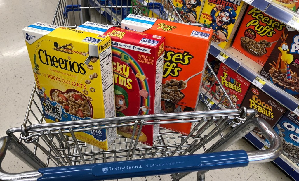 three boxes of cereal in a Walgreens cart