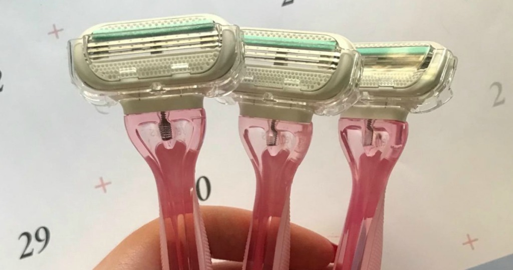Woman's hand holding three pink disposable razors