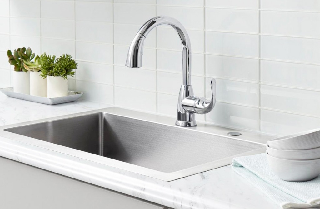 stainless steel kitchen faucet at stainless steel sink in marble counter