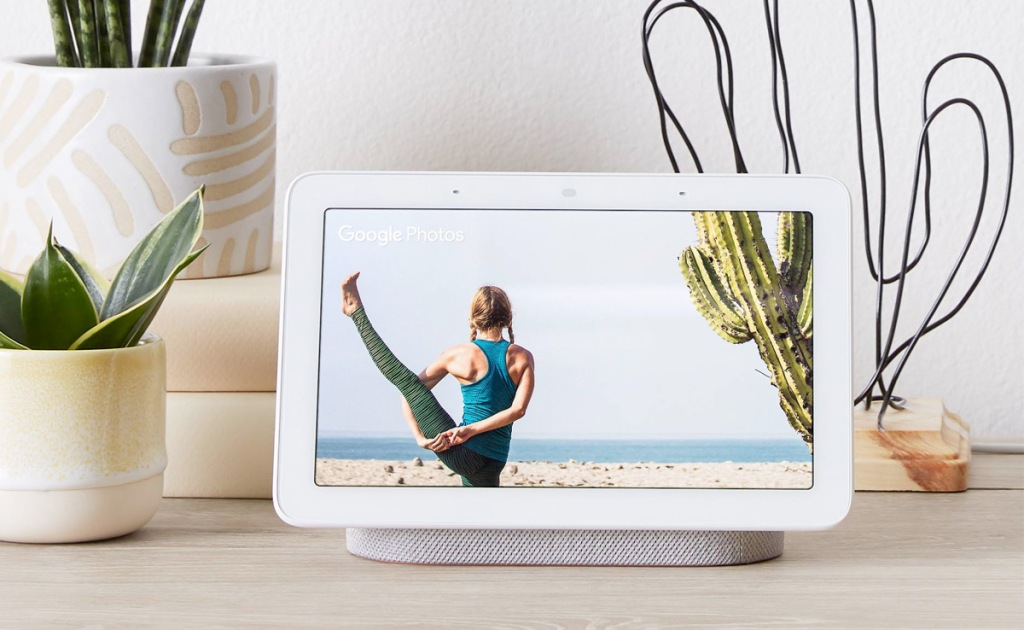 white google home smart display on table near potted succulents