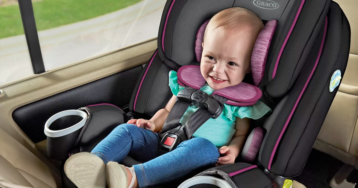 baby sitting in grey and pink car seat inside car