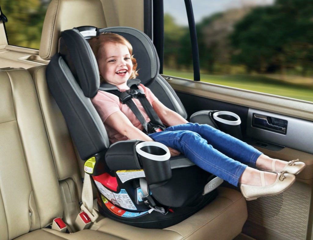 girl in black and grey car seat inside of car