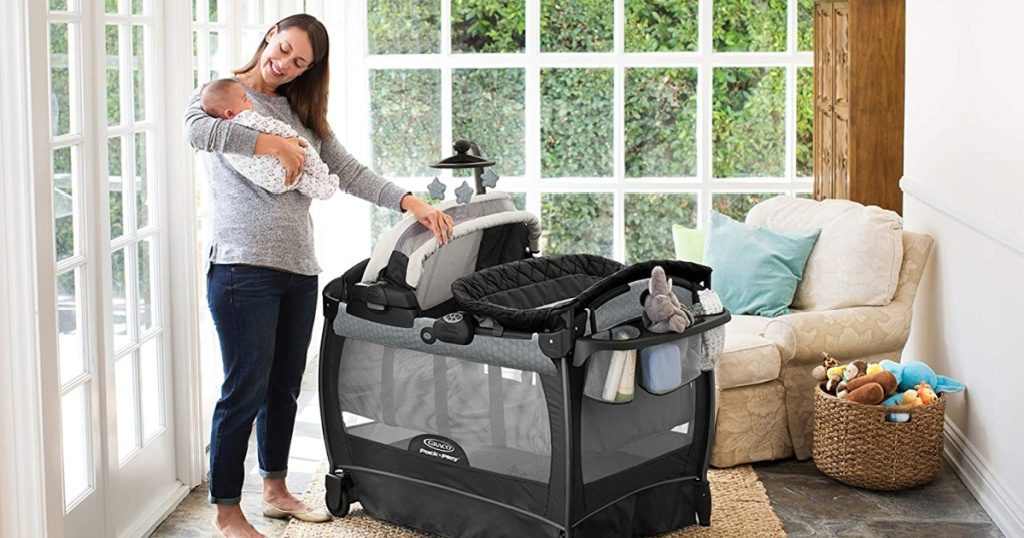 woman with baby standing by pack n play