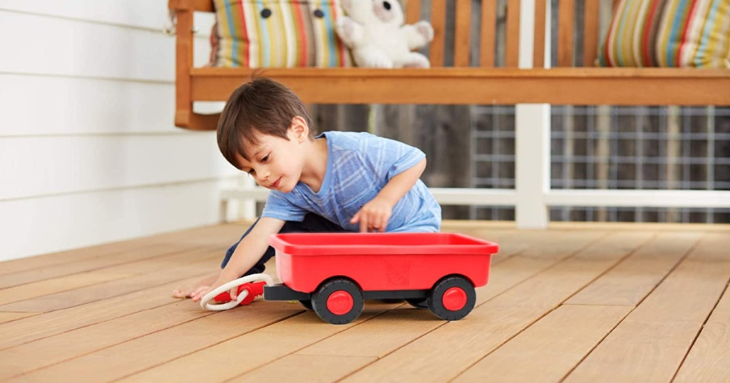 little boy playing with red wagon on deck