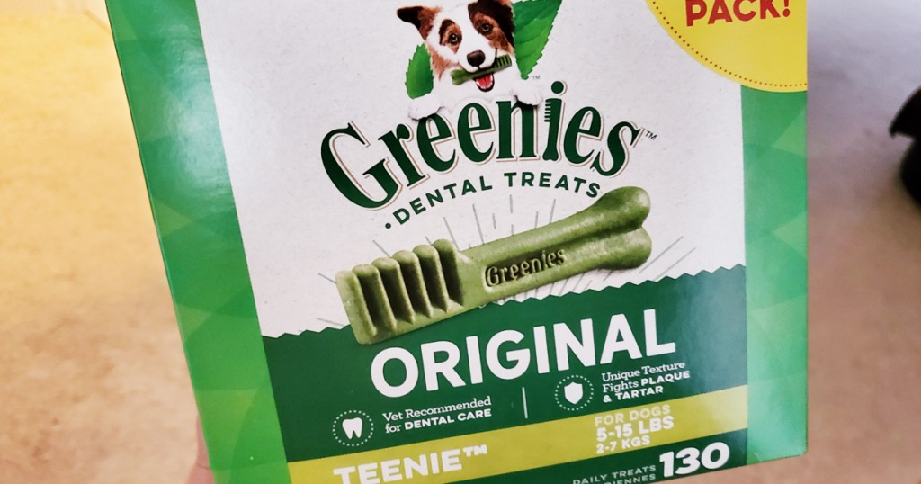person holding up a green and white box of greenies original dog treats