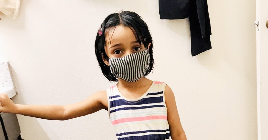 girl in striped dress wearing a black and white striped face mask