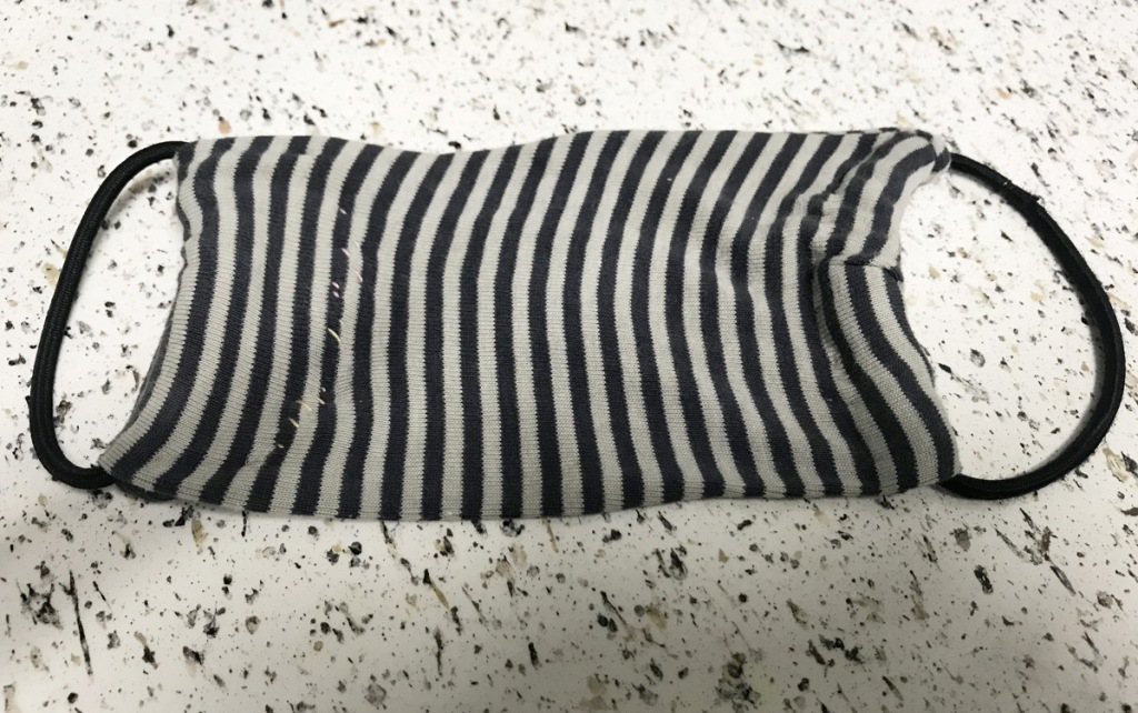 black and white striped face mask with black elastic ear loops