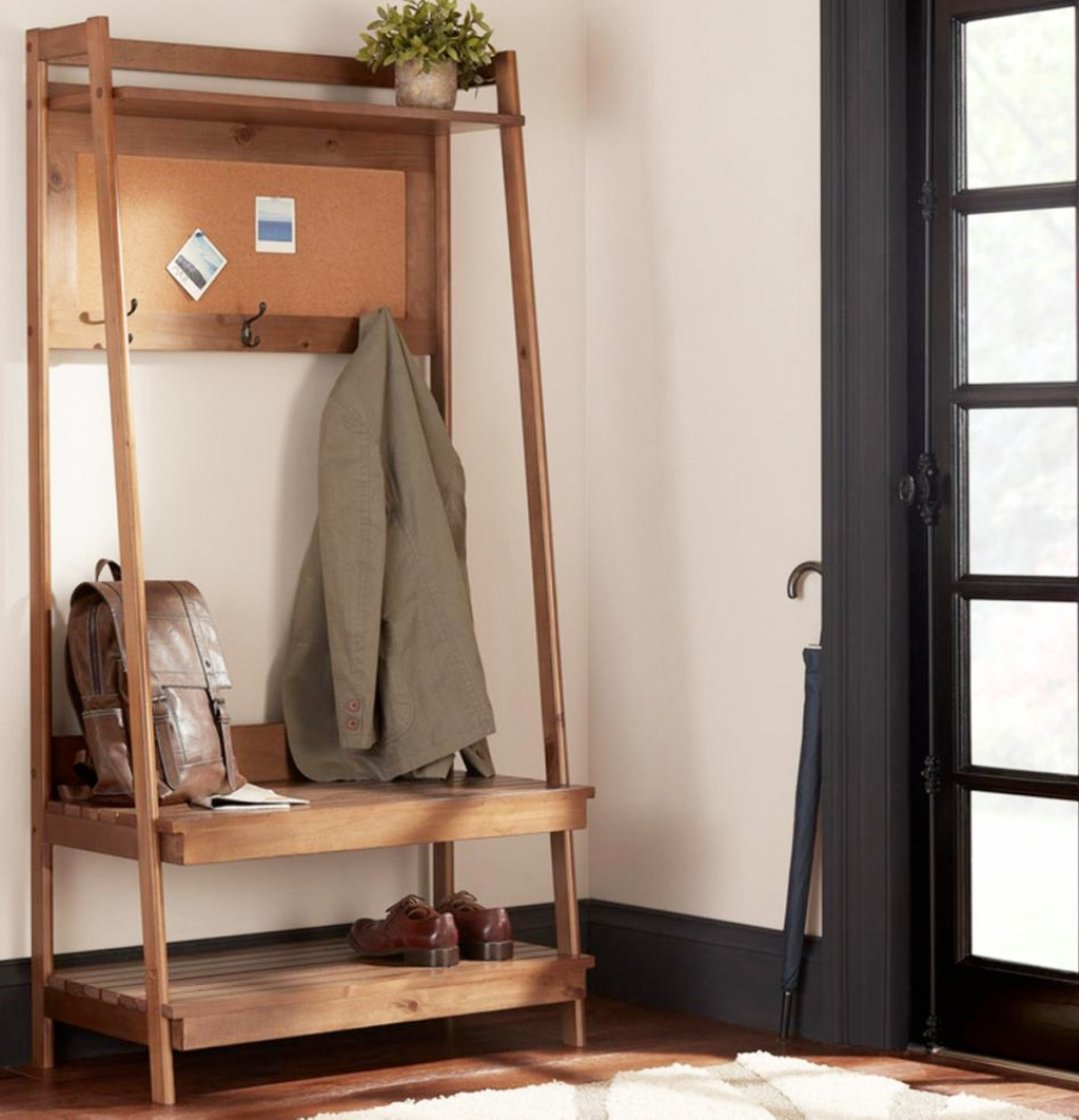 wooden open hall tree with bench, lower storage shelf, and jacket hanging from hook