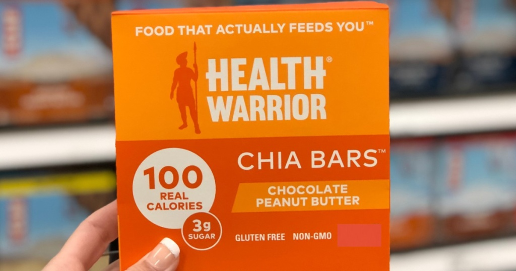 manicured hand holding box of chocolate peanut butter chia bars in store aisle