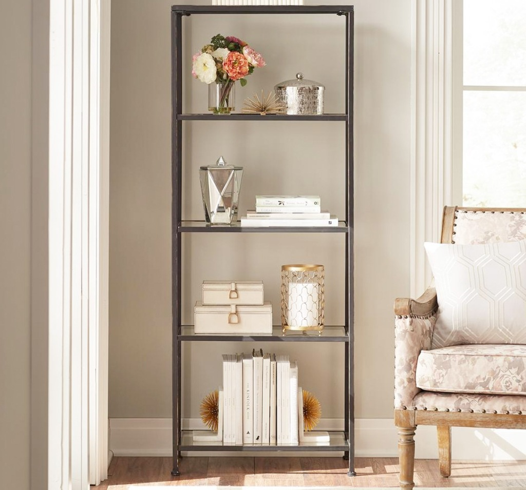 tall glass bookcase with bronzed metal frame in living room with trinkets and books on each shelf