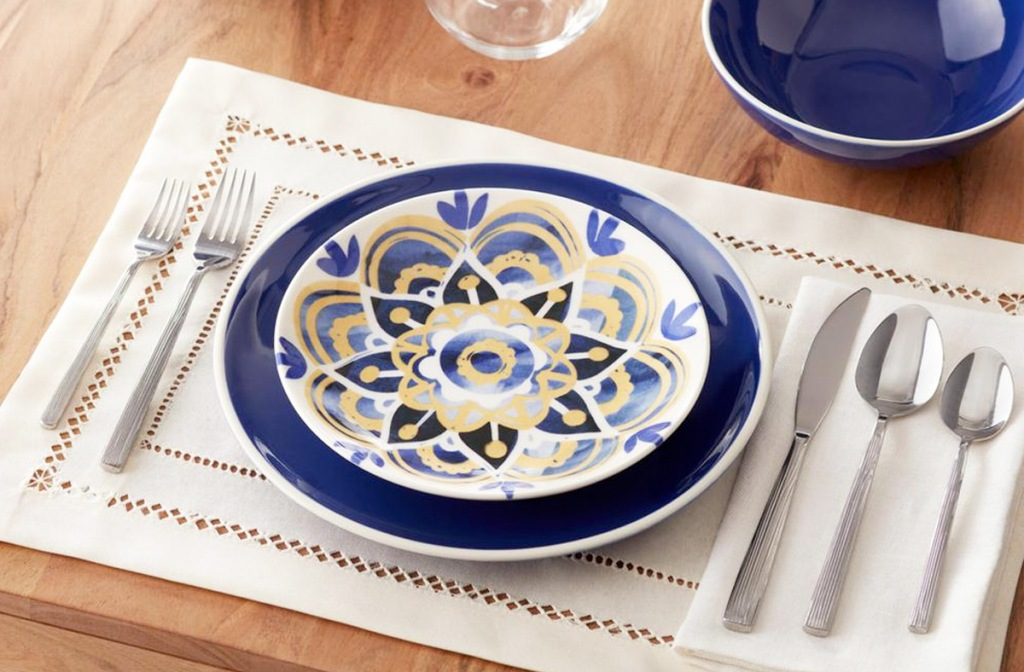 yellow and blue printed salad plate on a navy blue plate on wooden table with white placemat