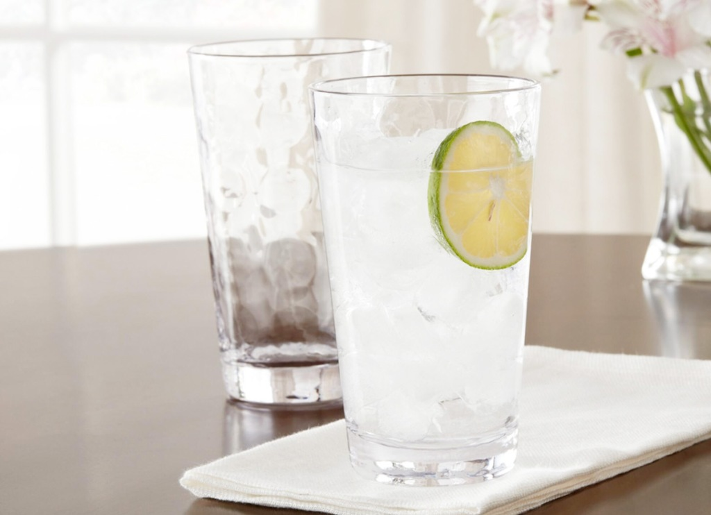 two glass tumblers on table, one filled with ice water with lime floating in it