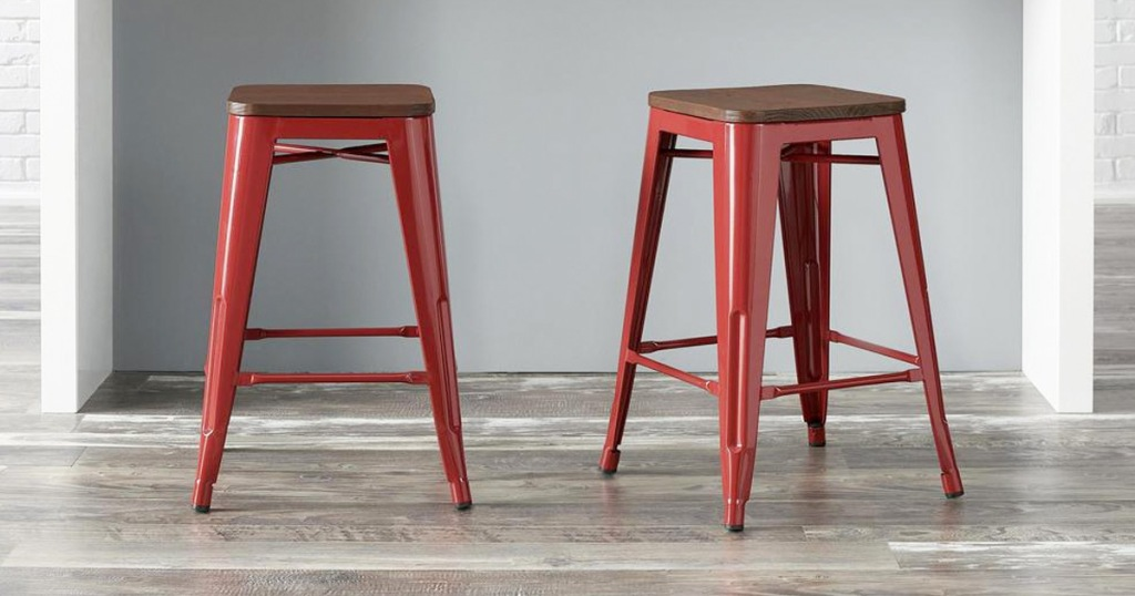 two red metal backless barstools with wooden seats