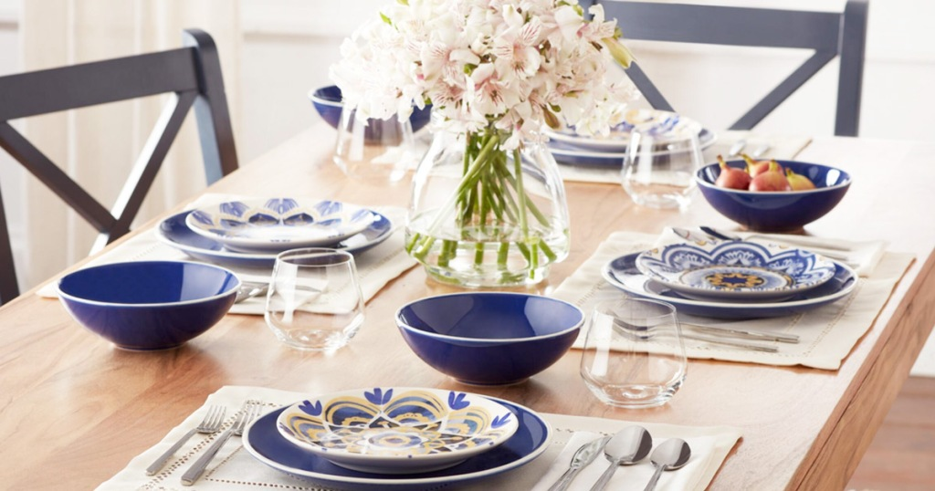 navy blue dinnerware set with four place settings on a wooden table with vase of flowers in the middle