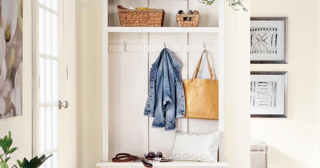 white wooden hall tree with bench, top storage shelf, and double hooks with hanging jacket and purse