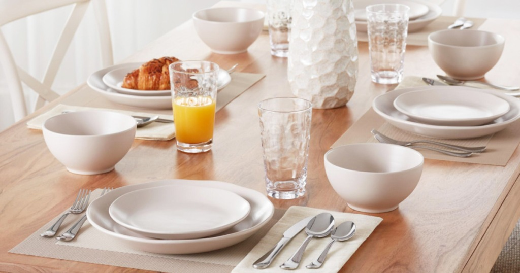 wood table set with multiple place settings with white plate sets, silverware, and glass tumblers