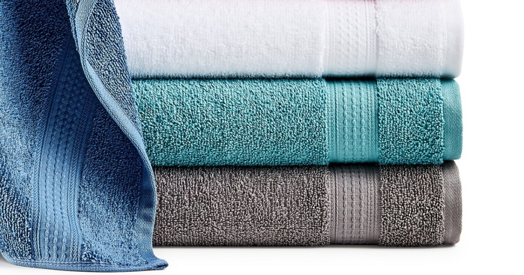 blue, teal, gray, and white bath towels folded in a pile