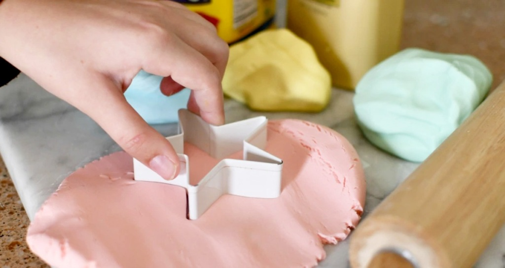person using a star shaped cookie cutter to cut into red colored play-dough