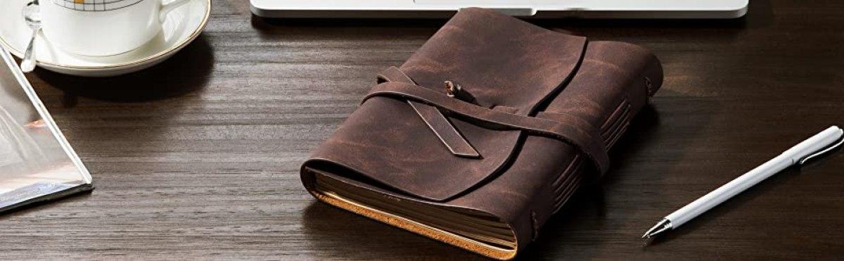journal on desk next to pen