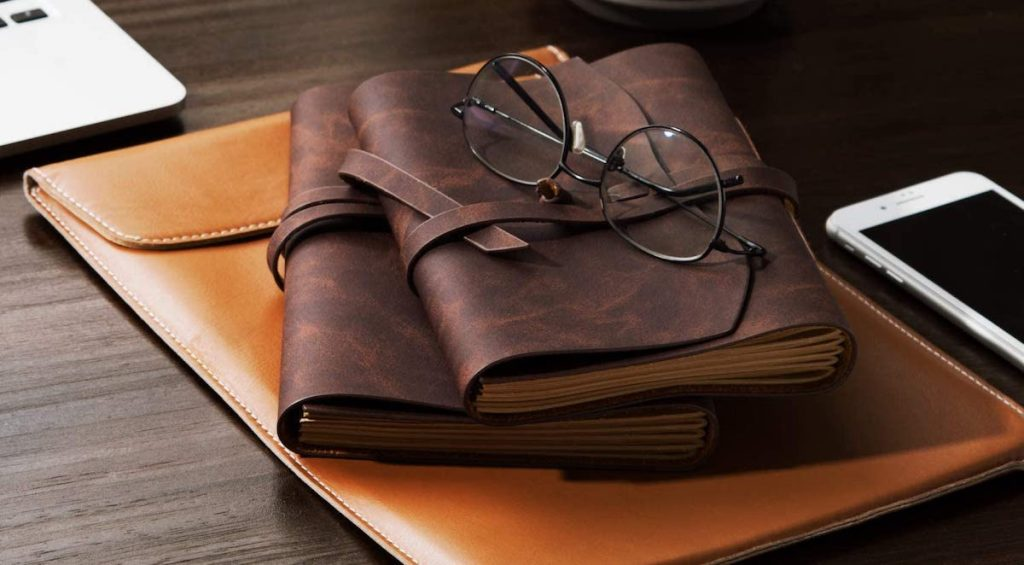 two leather journals sitting on a leather folder