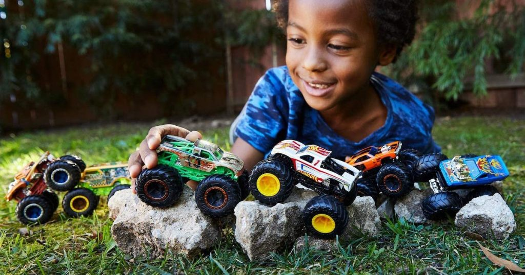 boy playing with hot wheels monster trucks on rocks outside