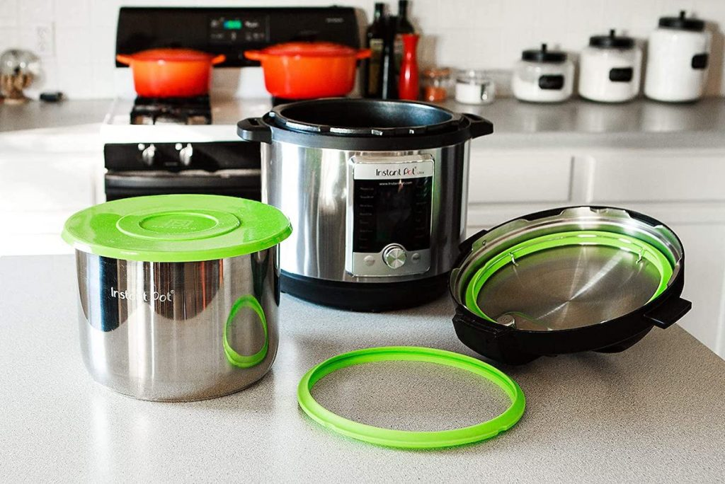 instant pot on kitchen counter with green silicone lid cover on pit and green silicone lid ring