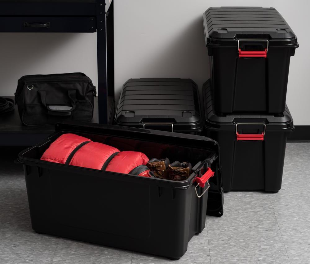storage bins on floor with a sleeping bag in one
