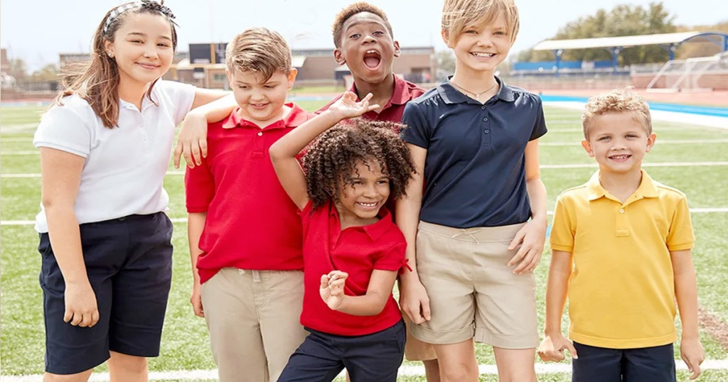 kids wearing school uniform pieces standing on football field