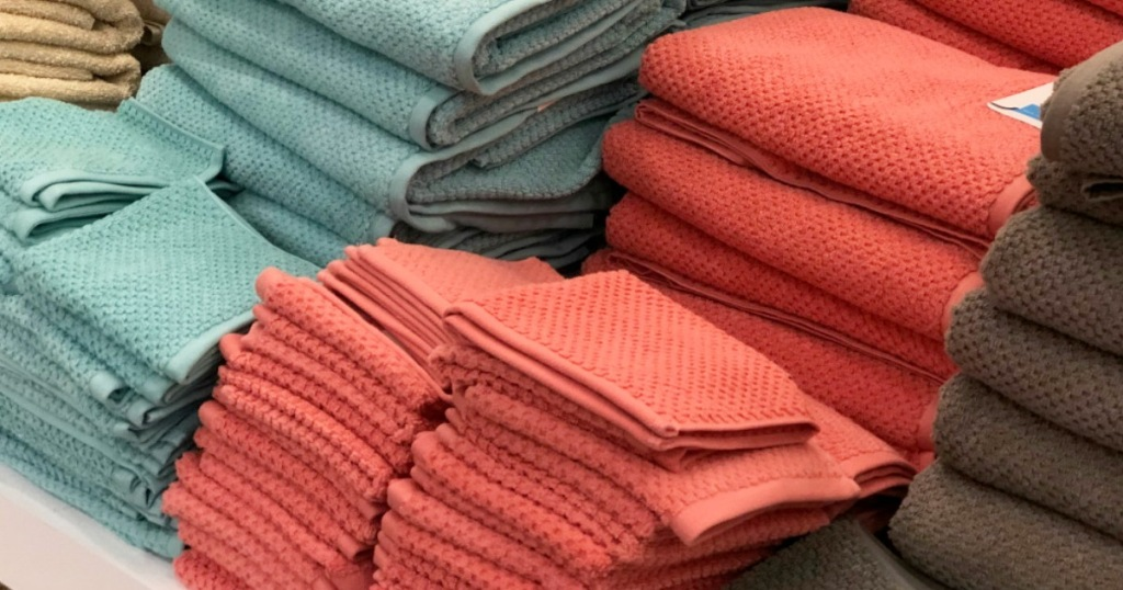 store display shelf full of textured bath and hand towels in blue, coral, and brown colors