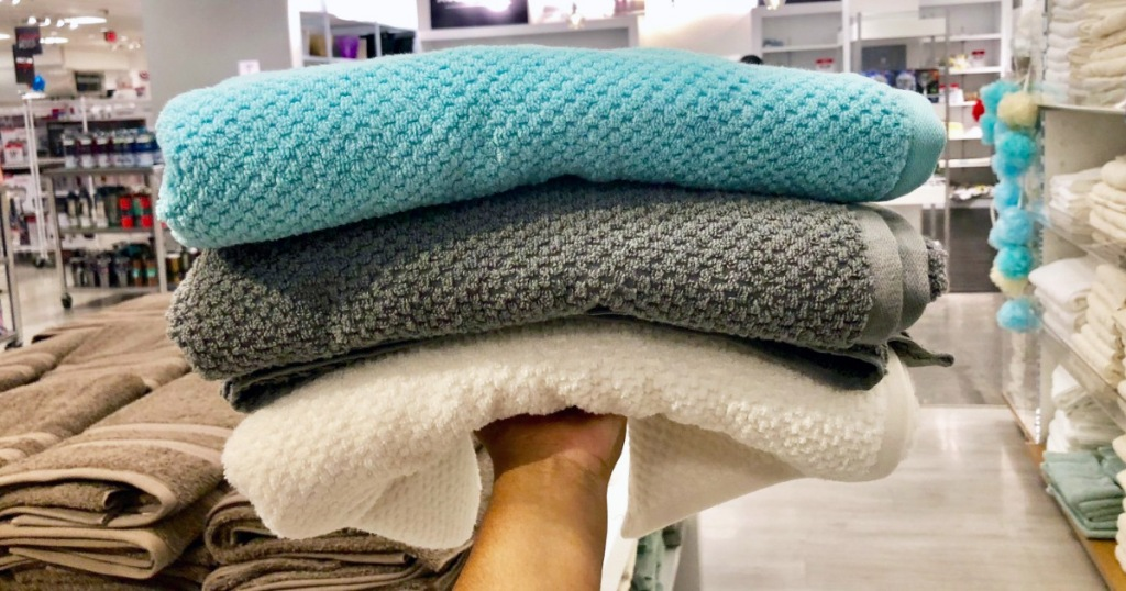 persons hand holding up three textured bath towels in blue, grey, and white colors