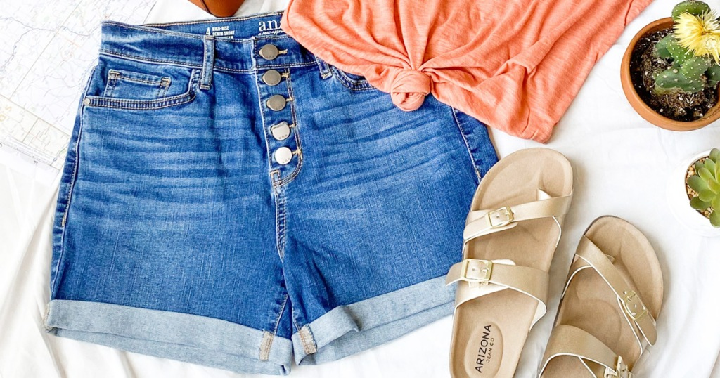 pair of denim womens shorts with five button closure placed next to an orange shirt and gold sandals