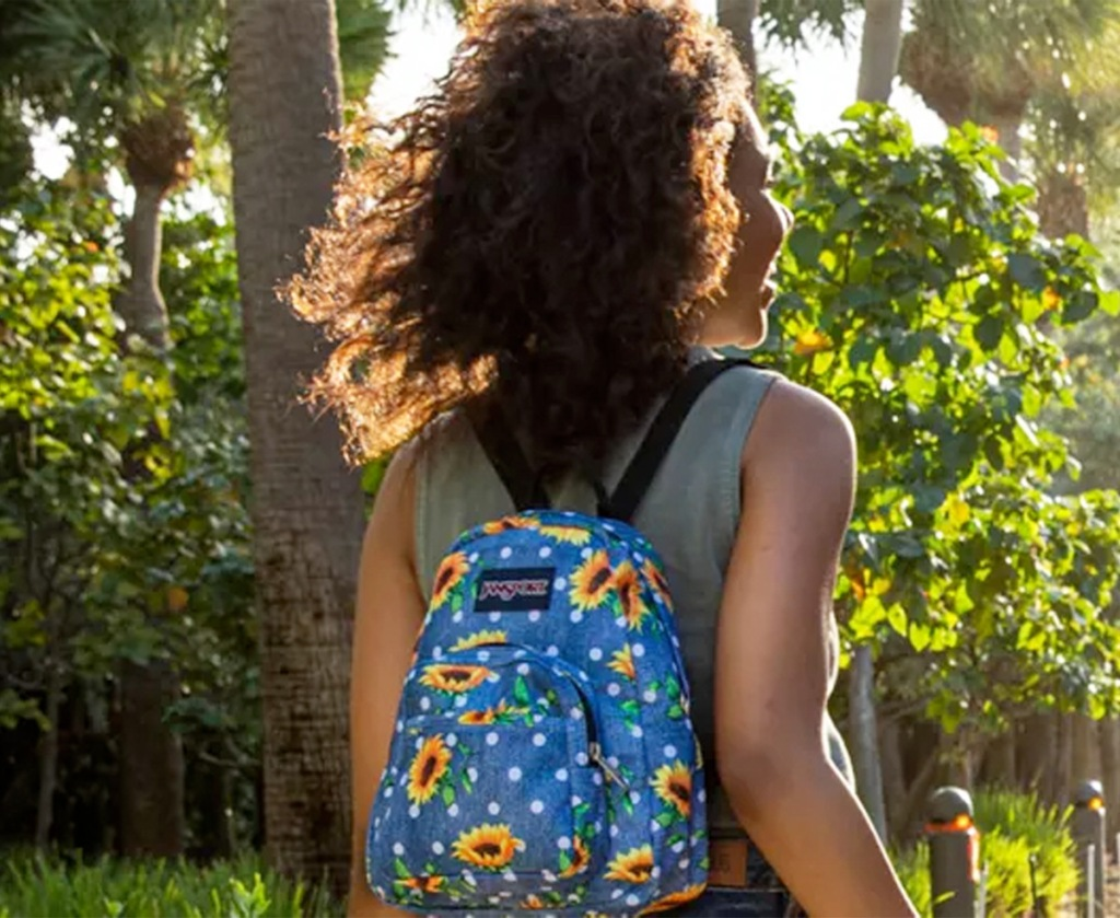 woman wearing a blue mini packpack with sunflower and white polka dot print