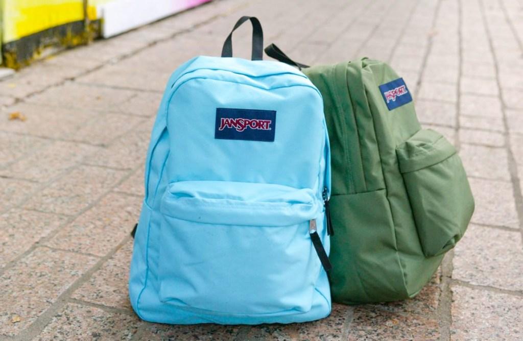 blue and green jansport brand backpacks sitting on sidewalk