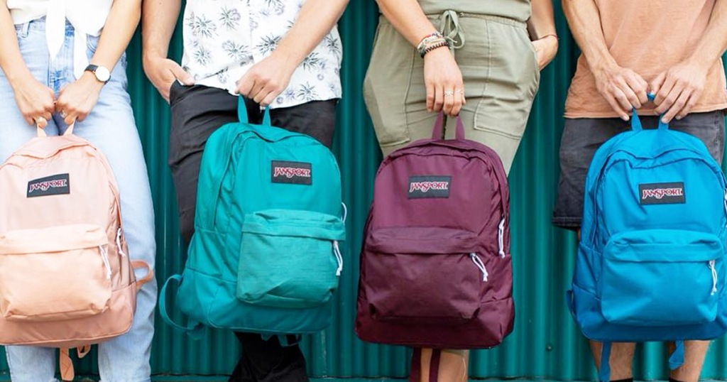 people standing against green wall holding jansport brand backpacks in front of them