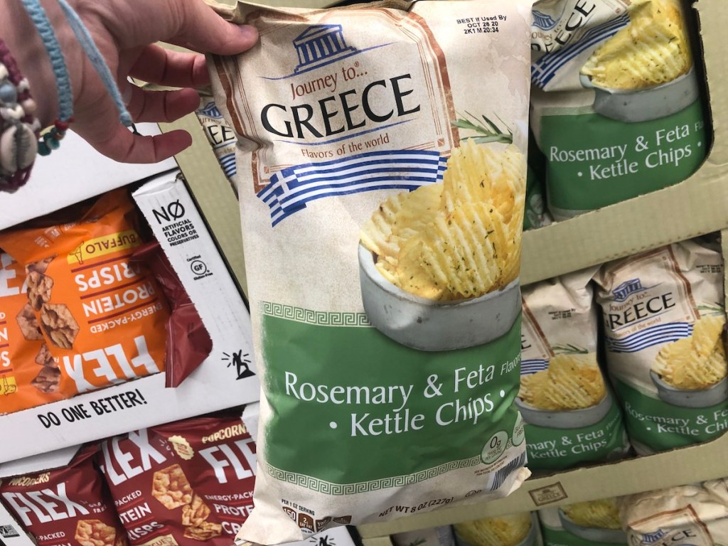 hand holding bag of Journey To... Greece Rosemary and Feta Krinkle Cut Kettle Chips