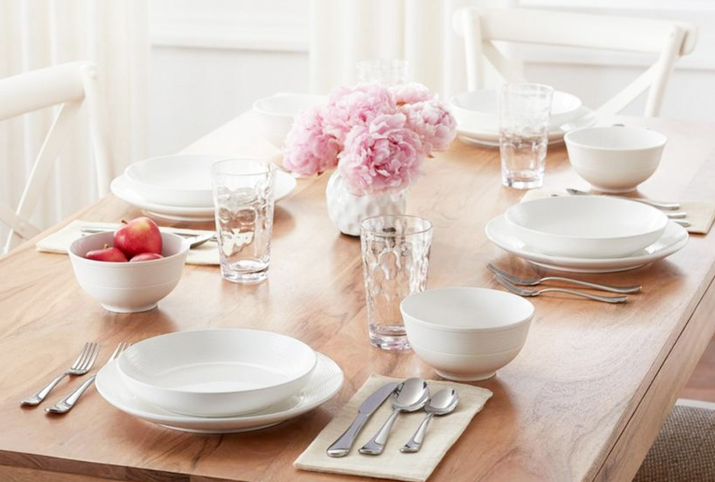 white dinnerware set on wooden table with white vase of pink flowers