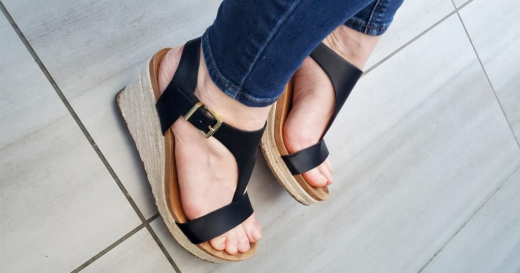 woman wearing a pair of black wedge sandals and skinny jeans