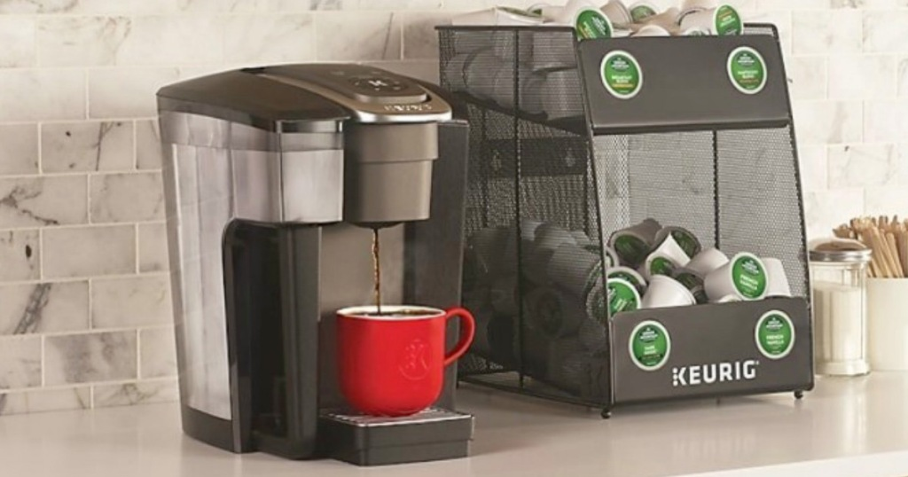 black keurig brewer on counter with red coffee cup and black storage bin full of k-cup pods next to it