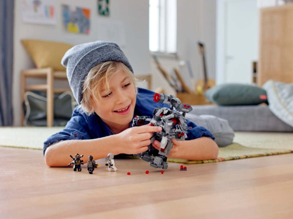 Kid playing with a LEGO Marvel Avengers War Machine Buster Superhero Mech Building Set