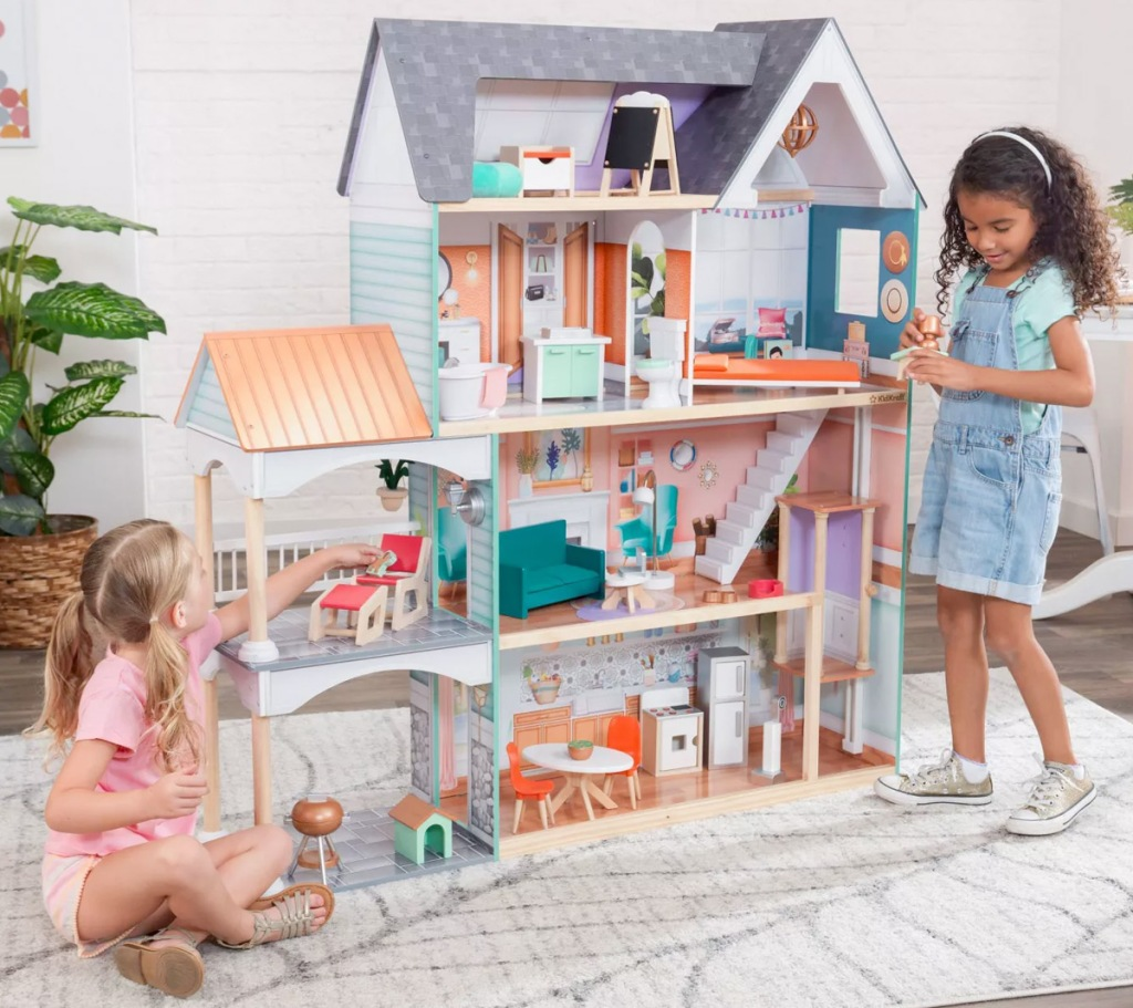 two girls playing with large mansion dollhouse with furniture in each room