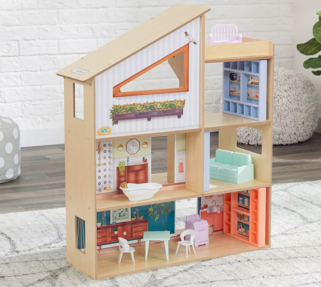 wooden dollhouse sitting on area rug with furniture in each room