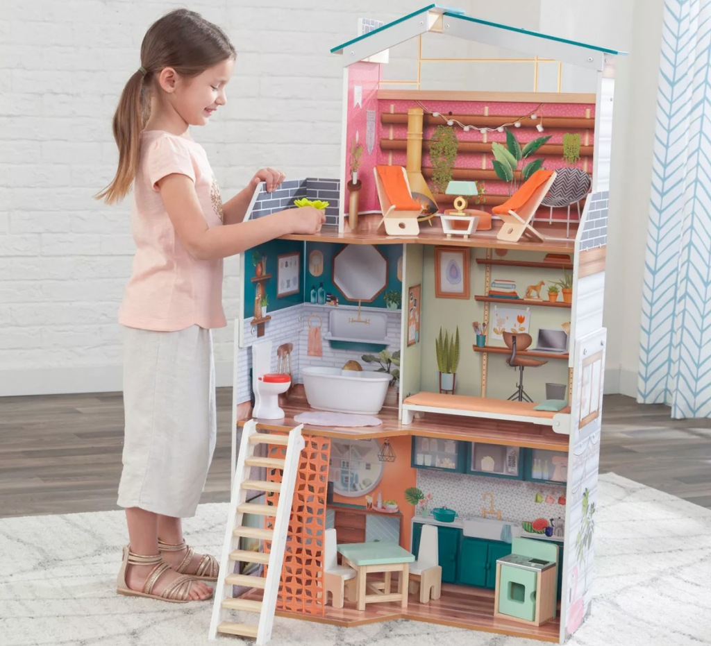girl standing next to large dollhouse the same height as her, with furniture in each room