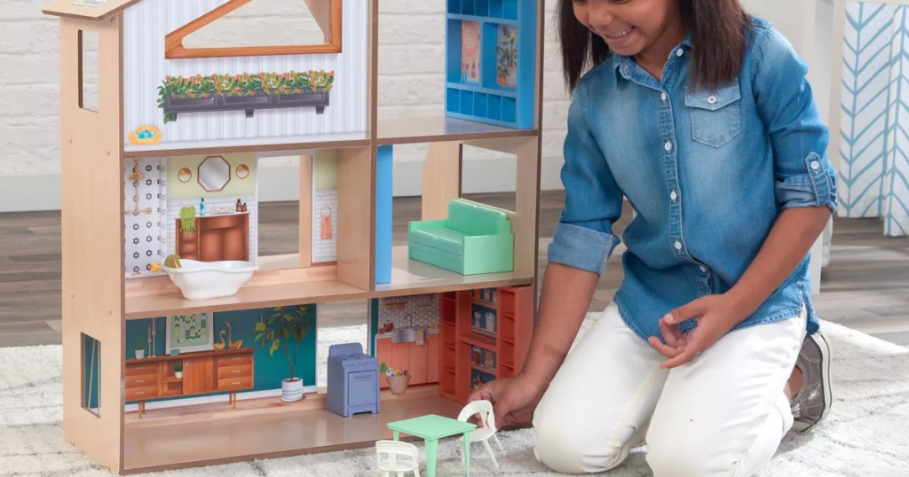 girl kneeling on floor next to wooden dollhouse playing with doll table and chair set