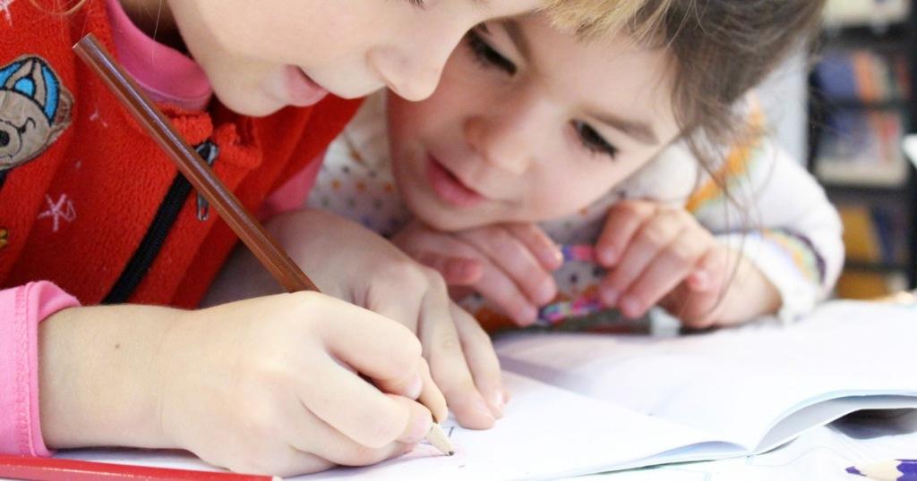 two young kids using colored pencils to draw in workbook