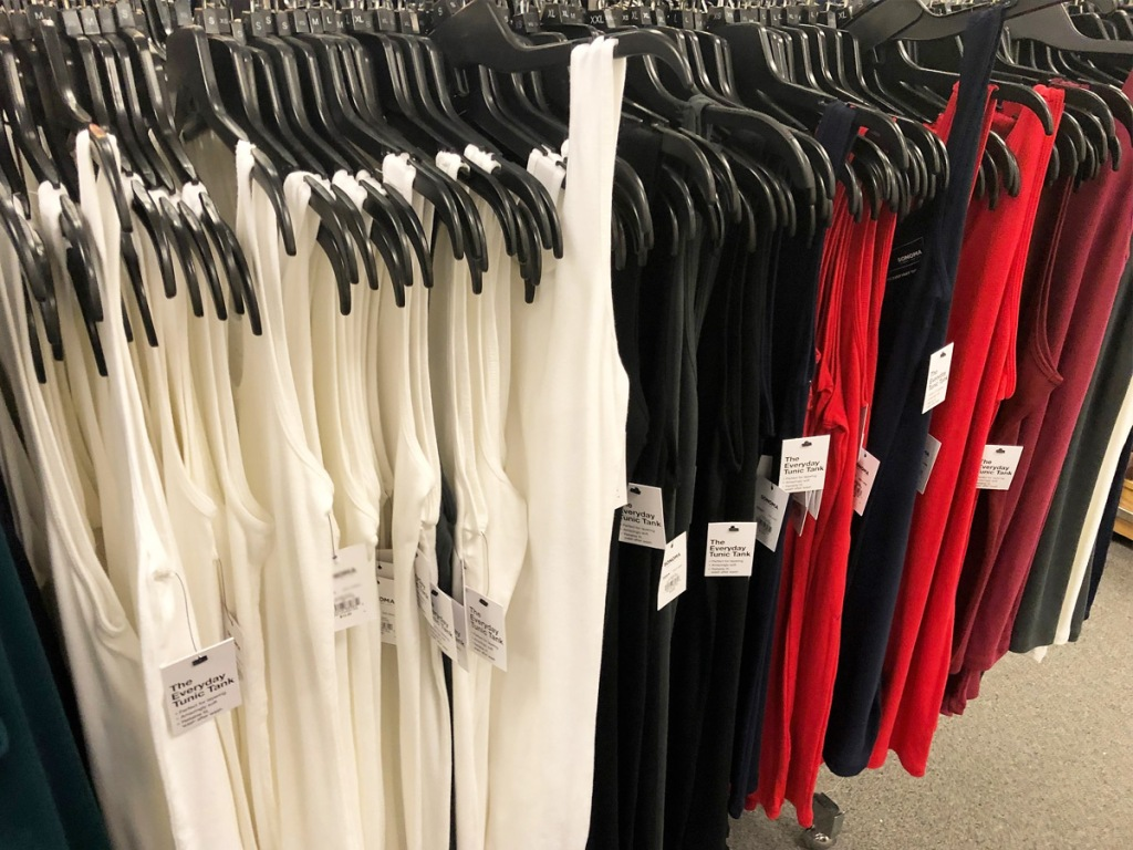 womens basic tank tops hanging on black hangers on store display rack