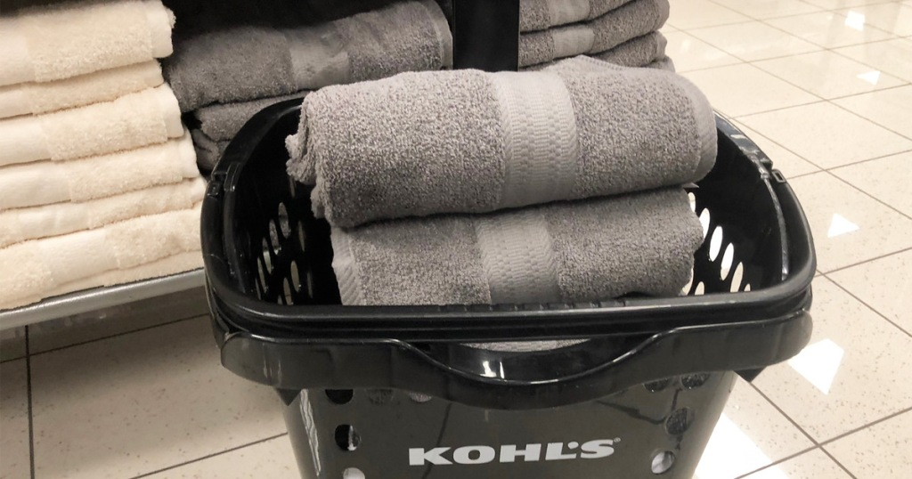 black kohls shopping basket with grey towels inside near display shelf of towels