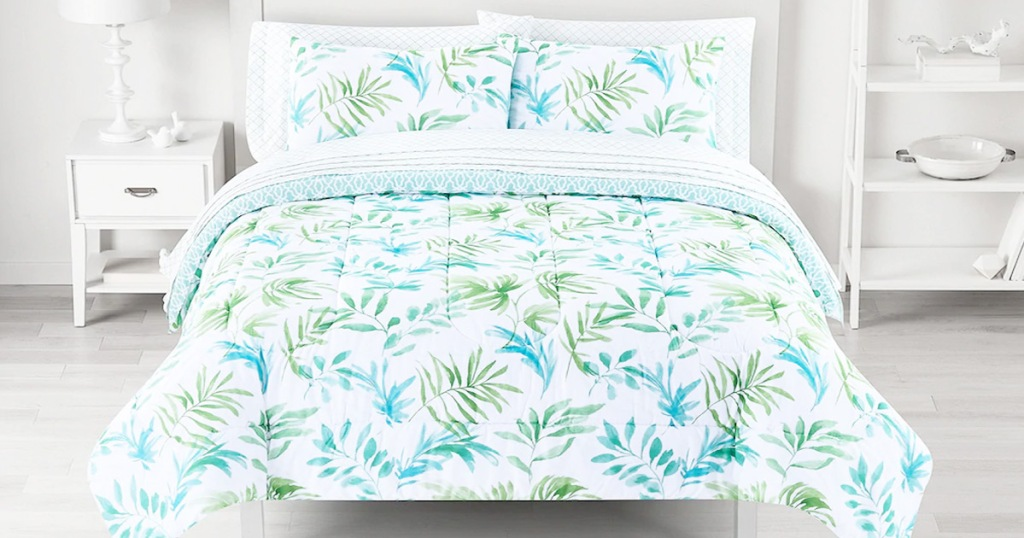 bed with white comforter set with blue and green palm print and matching pillow shams