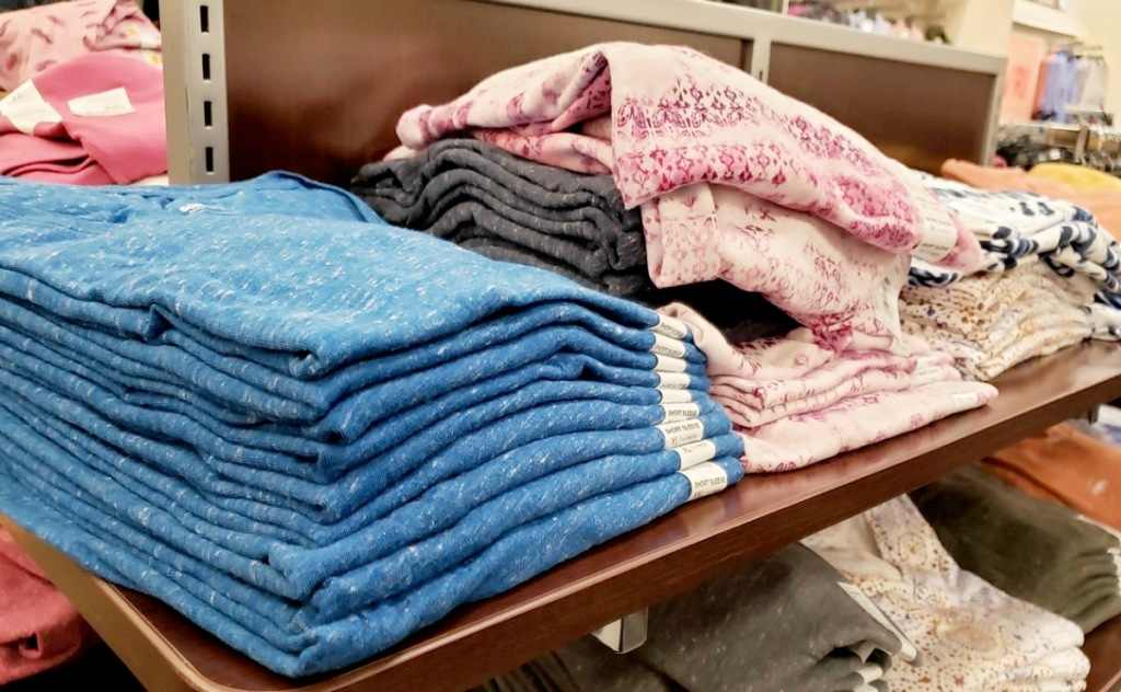 store display shelf with folded women's tees in various colors and prints