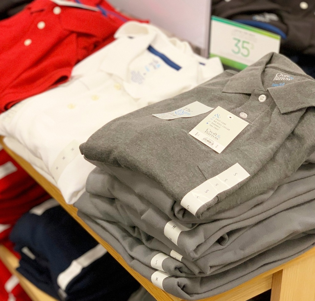 store display shelf filled with folded mens polo shirts in grey, white and red colors